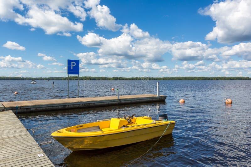 Barco de motor amarillo en el embarcadero del lago imagen de archivo libre de regalías