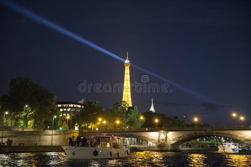 Barco de motor con los turistas delante del puente en el ri del Sena fotografía de archivo