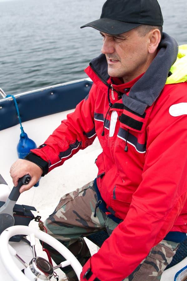 Barco de motor da direcção do homem fotografia de stock