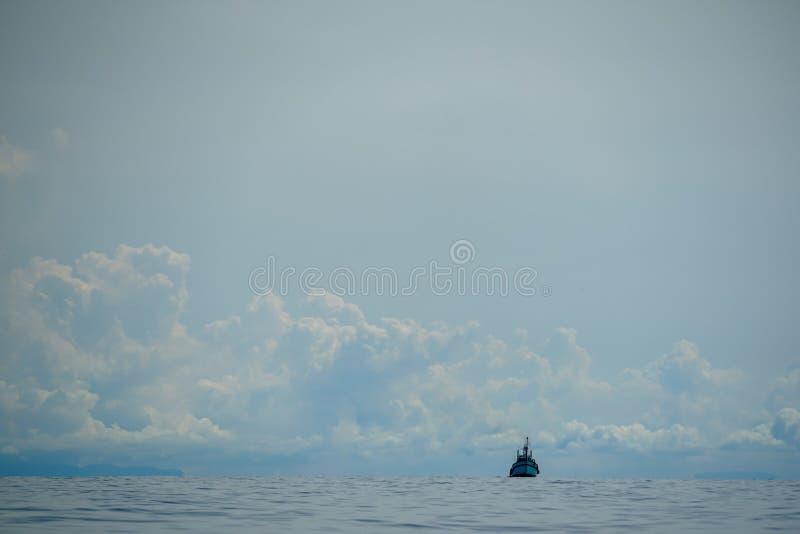 Barco de motor del pescador que navega independientemente en el océano extenso en onda ligera del mar con el fondo de la nube bla fotos de archivo libres de regalías