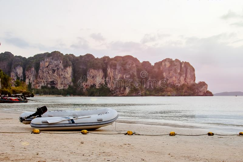 Barco de motor inflável com remos Em um Sandy Beach contra o contexto das montanhas e do mar fotografia de stock