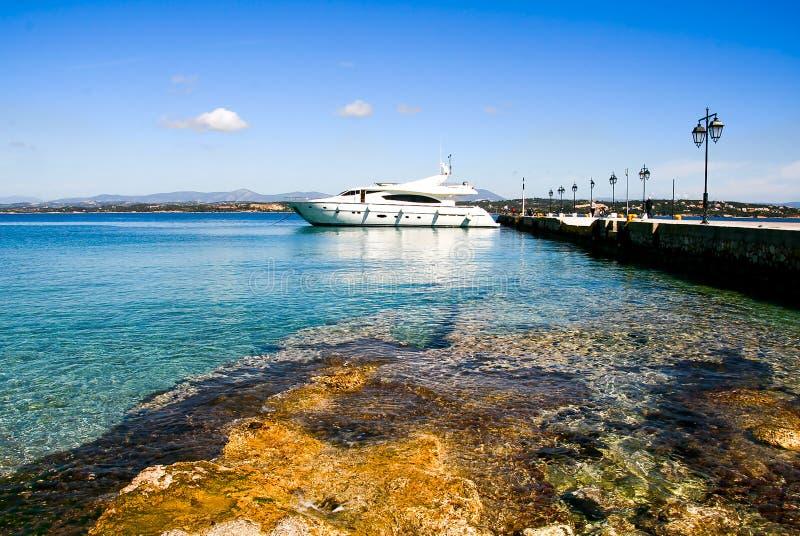 Barco de motor luxuoso e o cais no porto da ilha de Spetses, fotos de stock royalty free