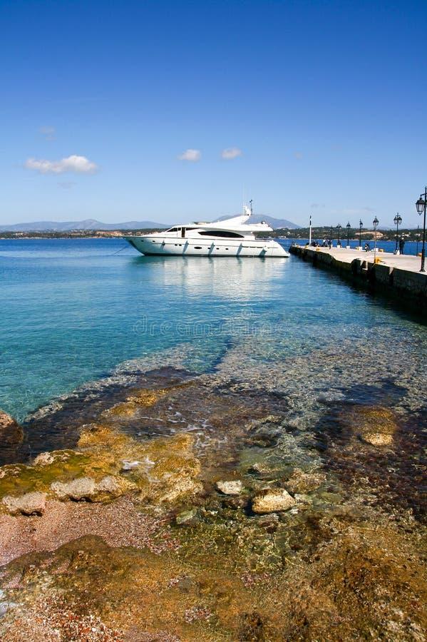 Barco de motor luxuoso e o cais no porto da ilha de Spetses, GR foto de stock