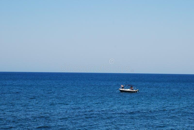 Barco de motor pequeno no mar azul imagem de stock