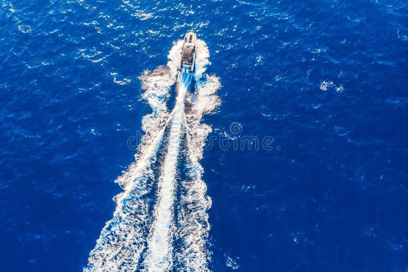 Barco de motor privado de lujo de la velocidad que sale del mar azul Visi?n superior a?rea imagen de archivo libre de regalías