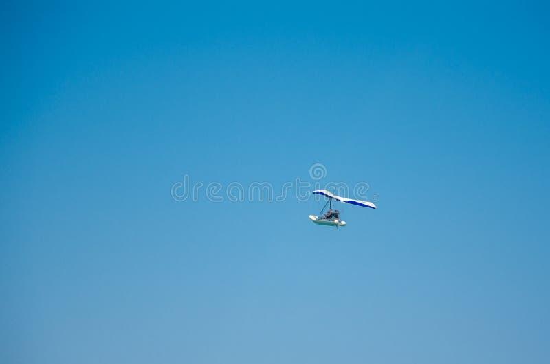 Barco de motor que vuela en el cielo azul claro fotos de archivo