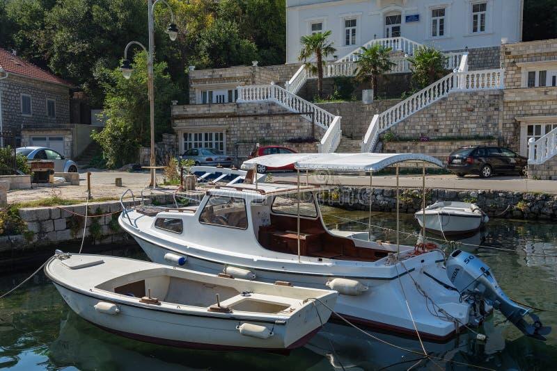 Barco de motor y barco que rema amarrado en el embarcadero en la costa fotografía de archivo