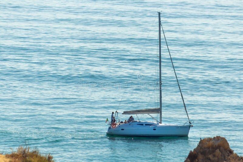 Barco de navegación anclado cerca de orilla y de rocas Lagos, Portugal fotos de archivo libres de regalías