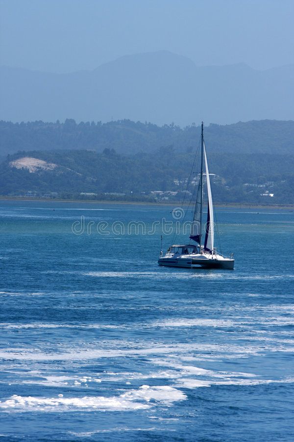Barco de navegación en el agua azul   fotografía de archivo libre de regalías
