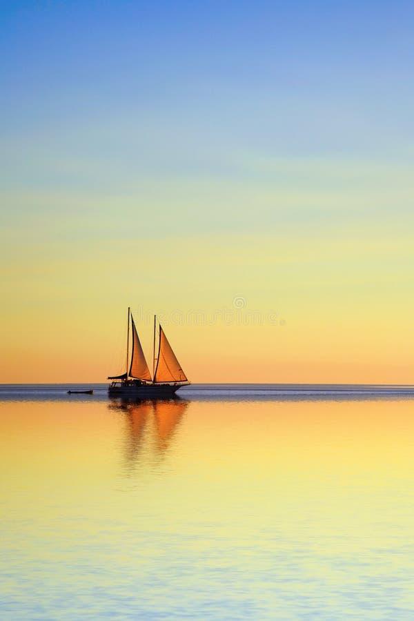 Barco de navegación en un océano tropical en el crepúsculo foto de archivo libre de regalías