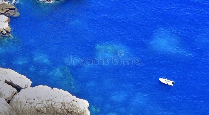 Barco de navegación en una bahía en la isla de Mallorca, rocas debajo del th imagen de archivo