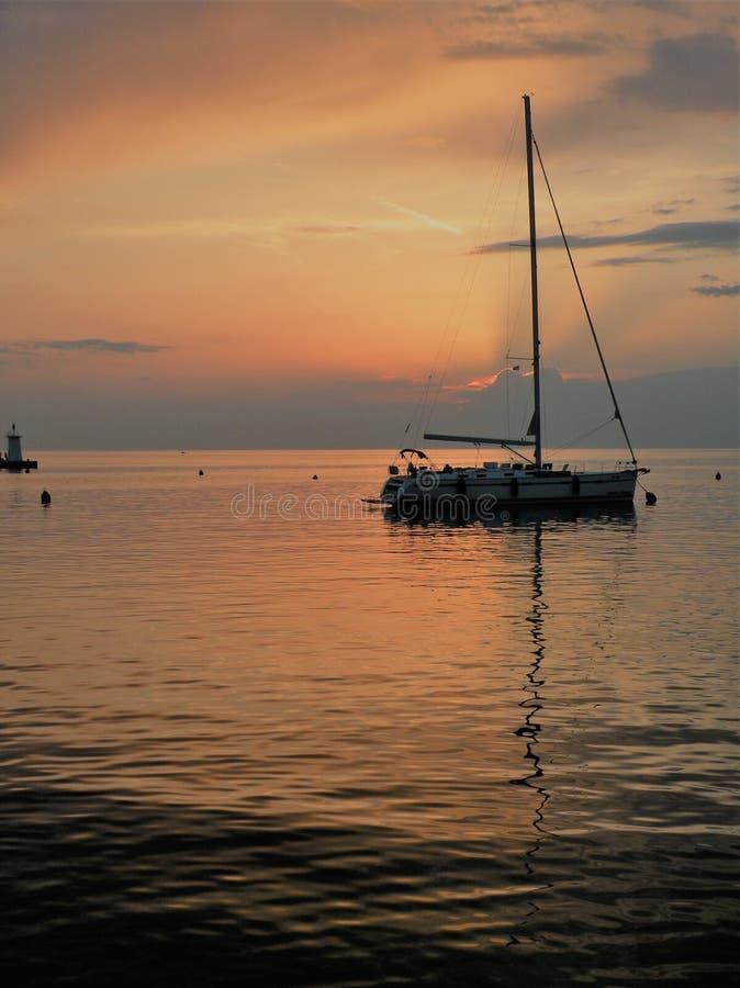 Barco de navegación que flota en una superficie pacífica del mar theAdriatic, Croacia, Europa Puesta del sol y el mar tranquilo c fotos de archivo