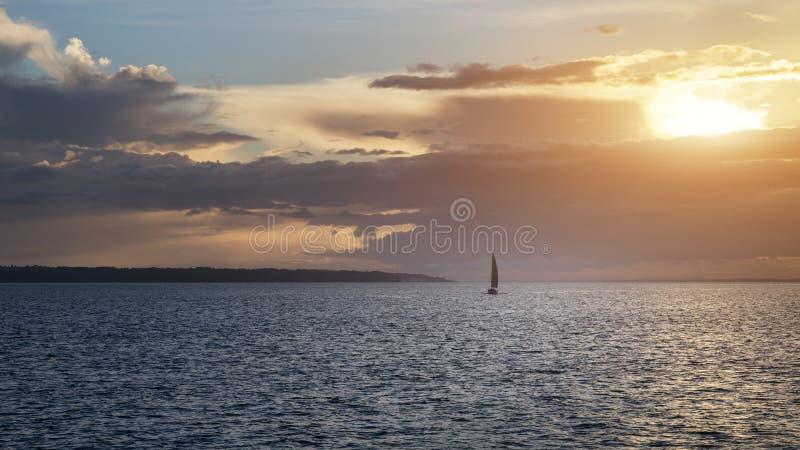 Barco de navegación solitario en el océano durante puesta del sol colorida vibrante fotos de archivo libres de regalías