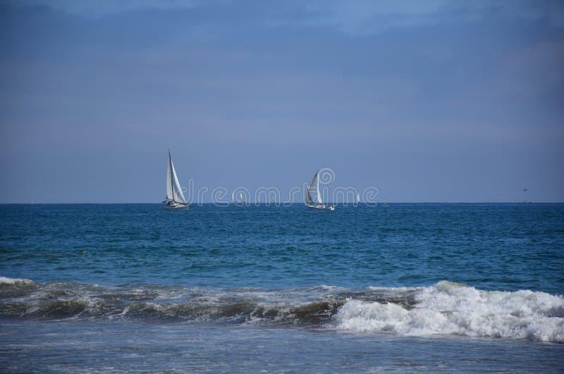 Barco de navigação calmo no oceano aberto na distância com mar azul fotografia de stock