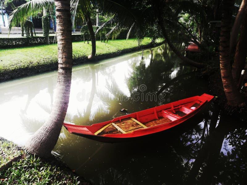 Barco de pá vermelho pequeno na lagoa fotografia de stock