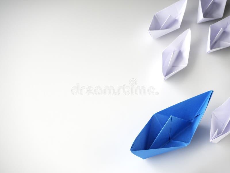Barco de papel azul que conduz entre os navios brancos imagens de stock