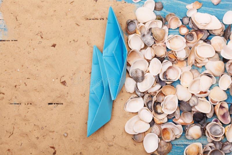 Barco de papel com shell e areia Fundo do vocação e do curso imagem de stock