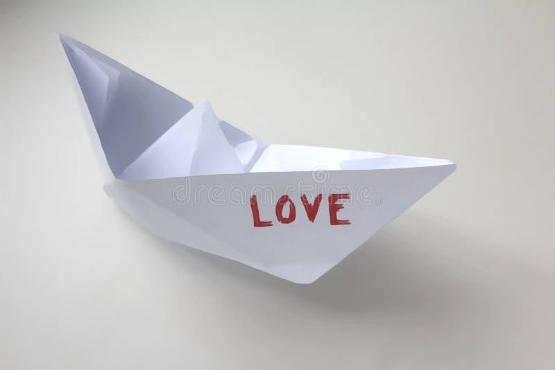 Barco de papel con la palabra 'amor ' imagenes de archivo