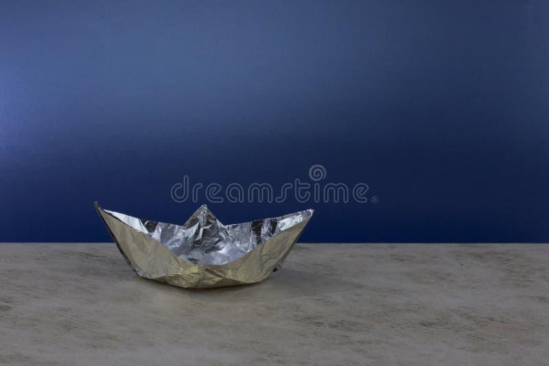 Barco de papel hecho del papel de aluminio imagenes de archivo