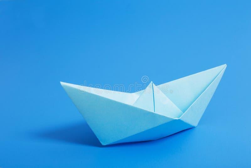 Barco de papel no fundo do papel azul fotografia de stock