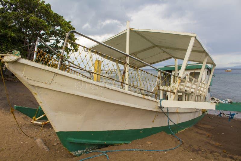 Barco de pasajero blanco en una arena de la playa Pequeño catamarán parqueado en una costa foto de archivo libre de regalías