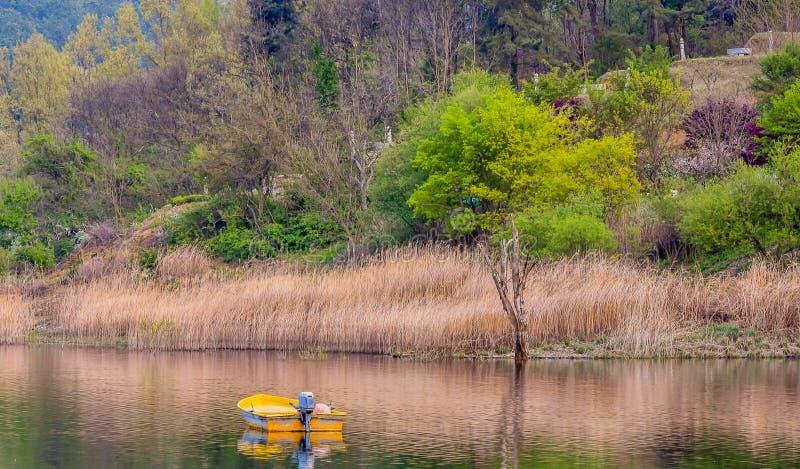 Barco de pesca amarillo que flota en el pequeño lago foto de archivo