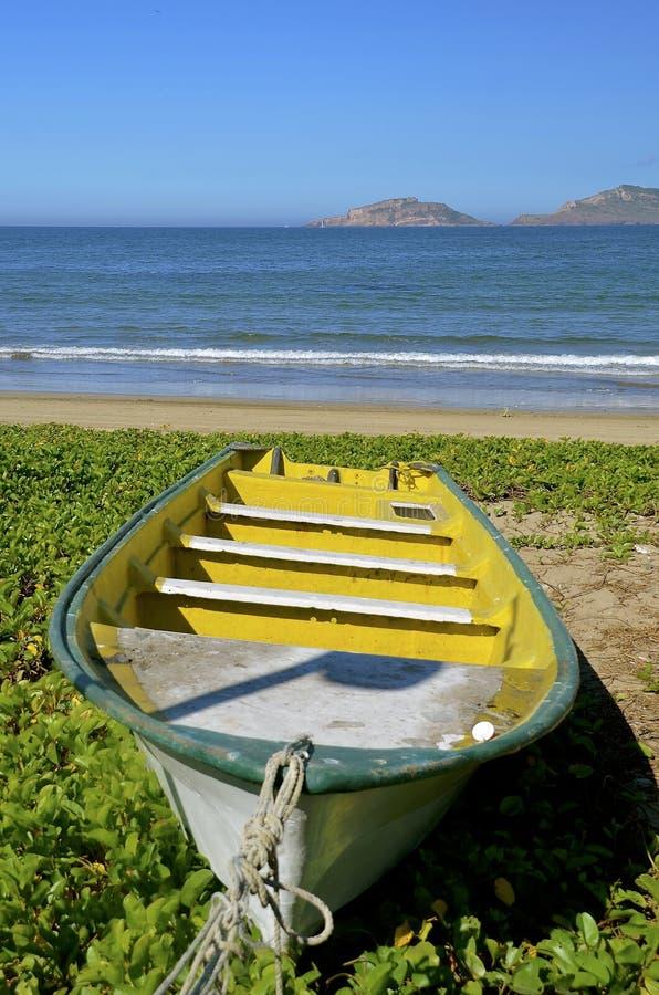 Barco de pesca amarillo viejo tirado en orilla fotos de archivo