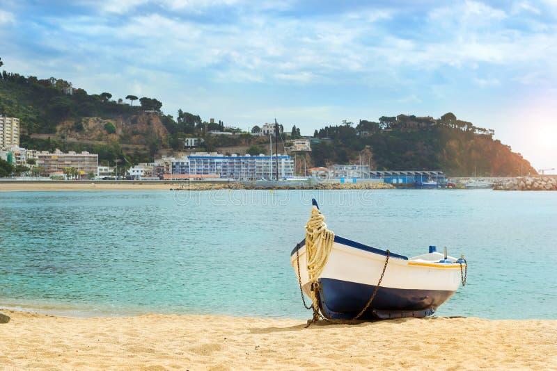 Barco de pesca amarrado en la playa arenosa Blanes, España fotos de archivo