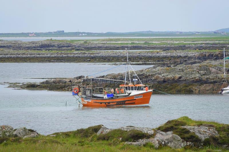 Barco de pesca amarrado en pequeña bahía imagen de archivo libre de regalías