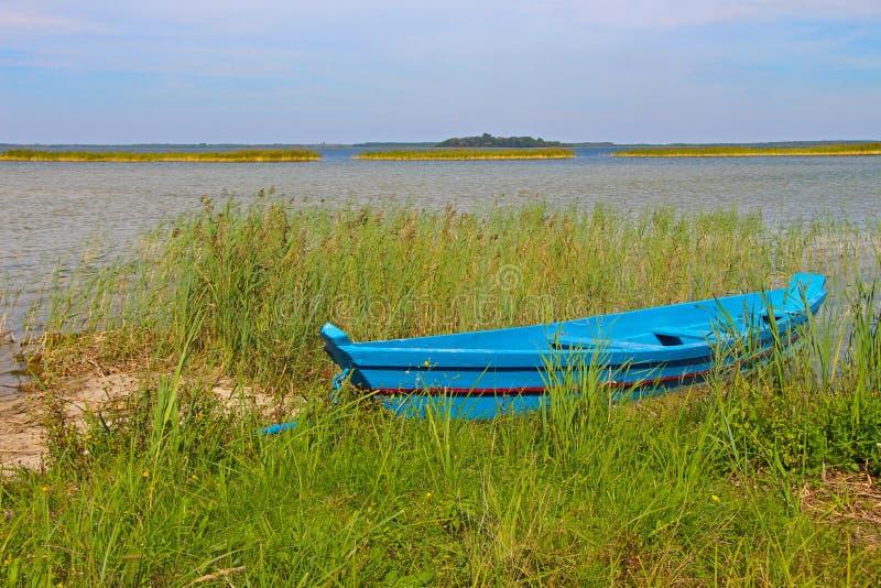 Barco de pesca azul de madera del viejo vintage en la hierba verde con horizonte imagen de archivo libre de regalías