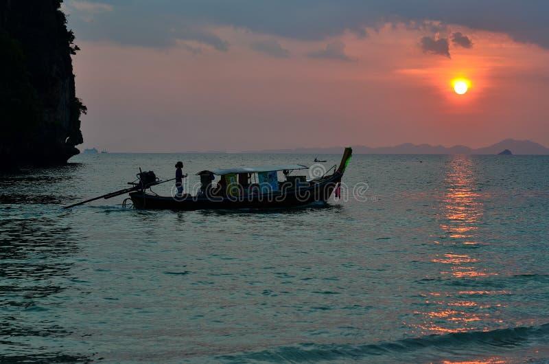 Barco de pesca com por do sol na praia de Railay fotos de stock royalty free