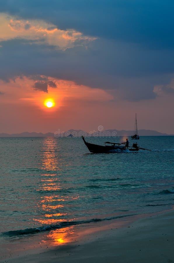 Barco de pesca com por do sol na praia de Railay fotos de stock
