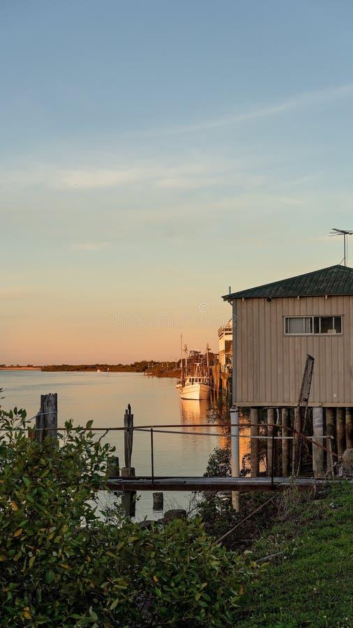 Barco de pesca comercial entrado no cais perto do por do sol fotografia de stock