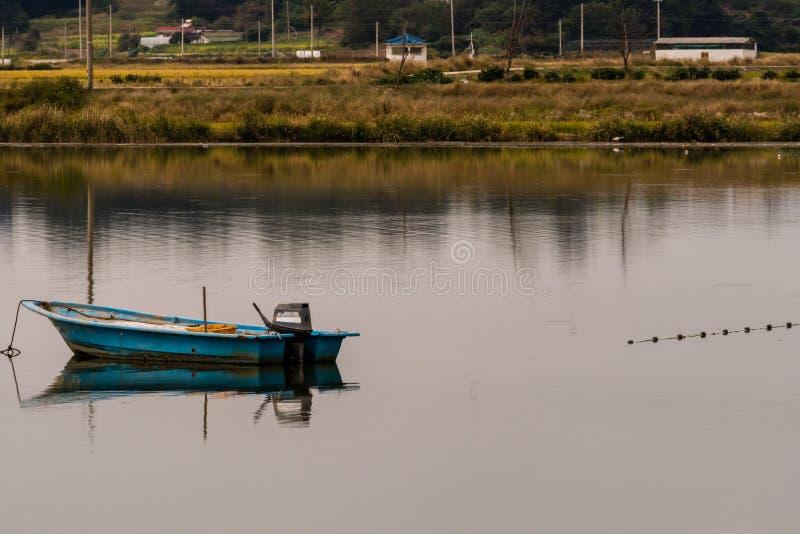 Barco de pesca con el motor externo en el centro del lago fotos de archivo