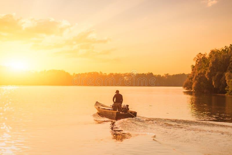 Barco de pesca da velocidade no rio com por do sol imagens de stock royalty free