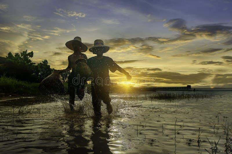 Barco de pesca do amanhecer, pescadores e pesca da criança na orelha foto de stock royalty free