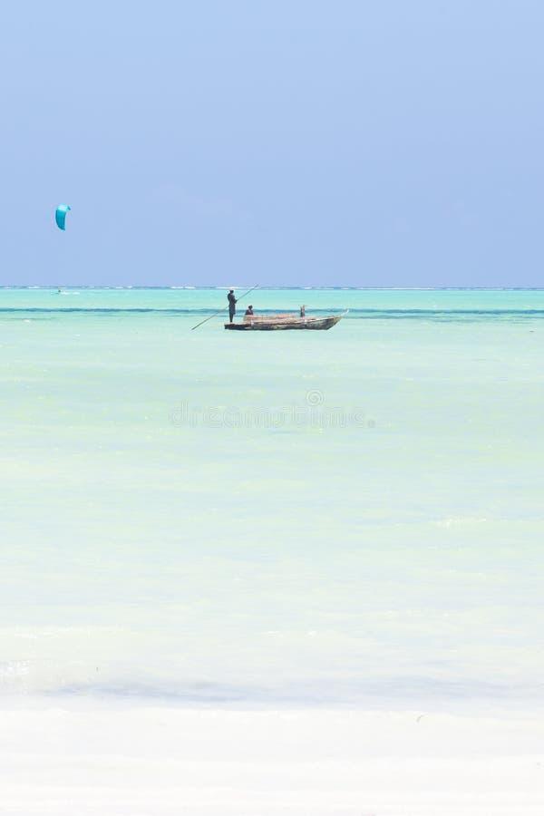 Barco de pesca e um surfista do papagaio no Sandy Beach branco perfeito da imagem com o mar do azul de turquesa, Paje, Zanzibar,  foto de stock
