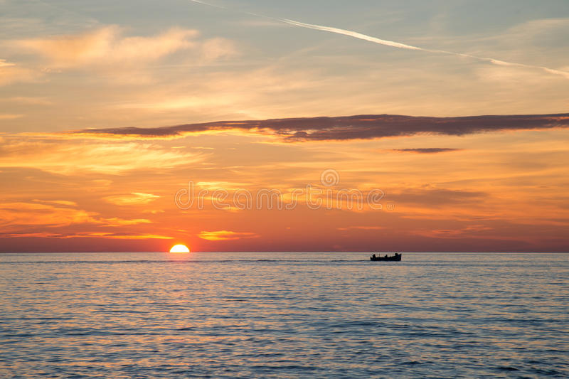 Barco de pesca en el fondo de la salida del sol de oro increíble, de nubes y del sol naciente fotos de archivo libres de regalías