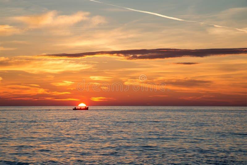 Barco de pesca en el fondo de la salida del sol de oro increíble, de nubes y del sol naciente foto de archivo