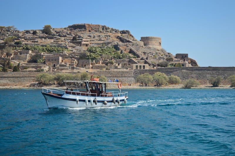 Barco de pesca en el mar con la isla y la fortaleza de Spinalonga en el fondo imágenes de archivo libres de regalías