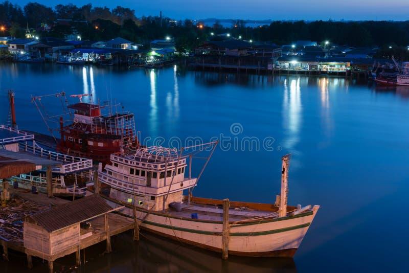Barco de pesca en el pueblo cerca del tiempo del crepúsculo del río foto de archivo libre de regalías