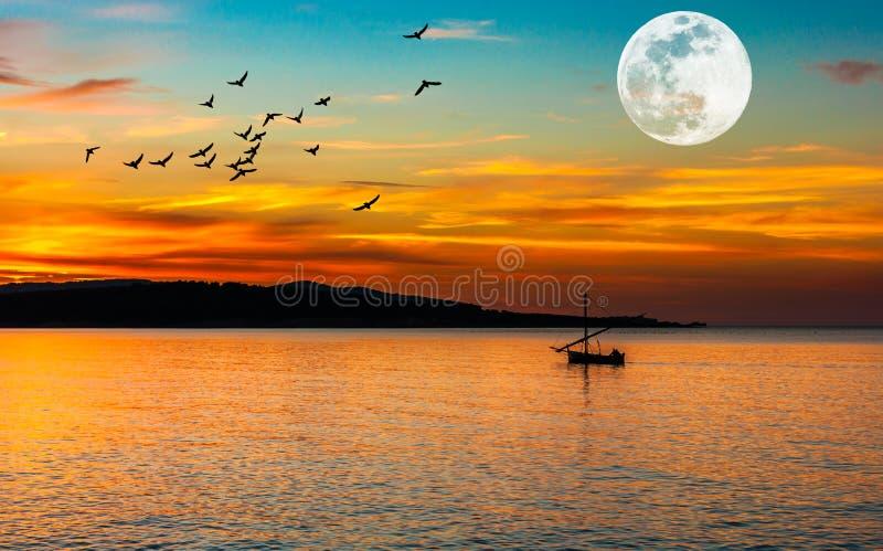 barco de pesca en la costa en la puesta del sol imagenes de archivo