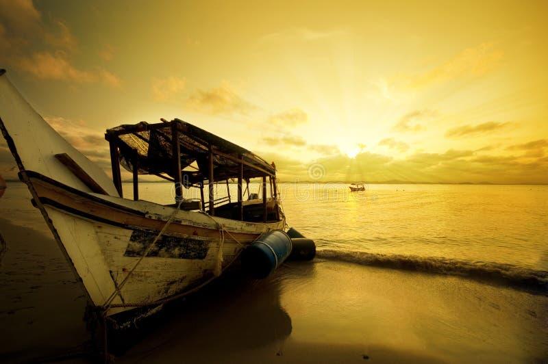Barco de pesca en puesta del sol imagenes de archivo