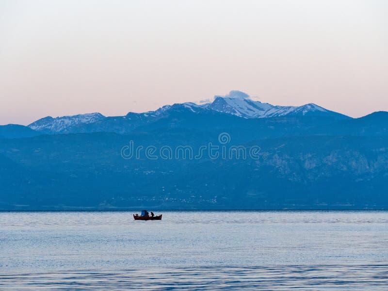 Barco de pesca grego vermelho pequeno e montanhas tampadas neve de Peloponnese, Grécia fotografia de stock