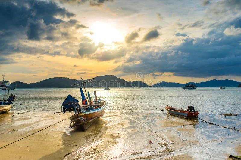 Barco de pesca local na praia no por do sol em Tailândia fotografia de stock royalty free