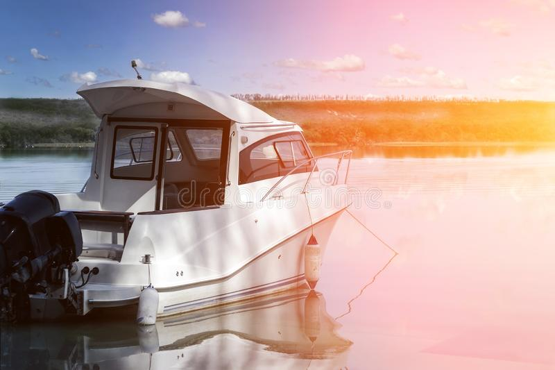 Barco de pesca luxuoso grande com a cabine amarrada perto da costa do rio ou do lago ainda na ?gua C?u azul no fundo ver?o fotografia de stock