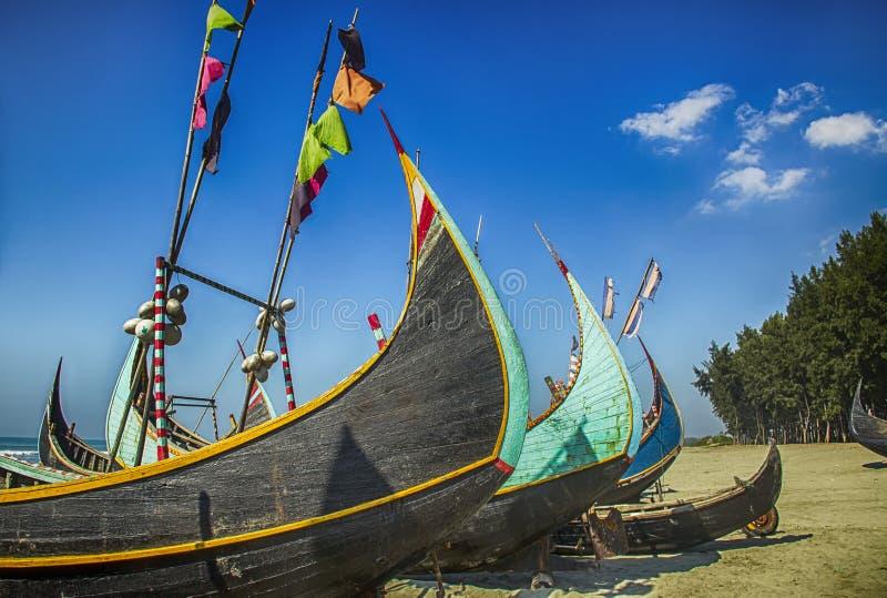 Barco de pesca de madeira em uma praia do mar de Coxbazar com fundo do céu azul em Bangladesh imagem de stock