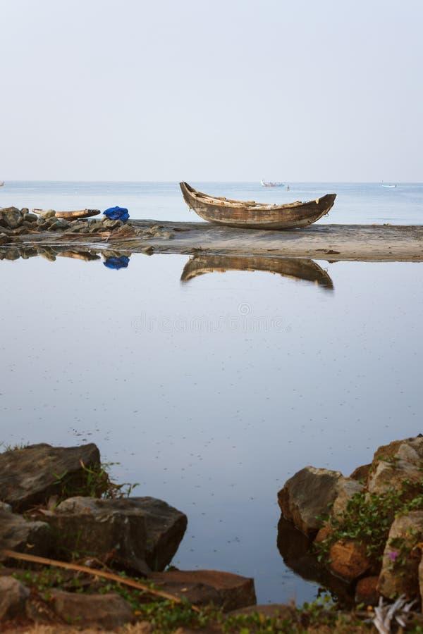 Barco de pesca de madeira só ancorado na reflexão da areia da praia nas marés fotografia de stock