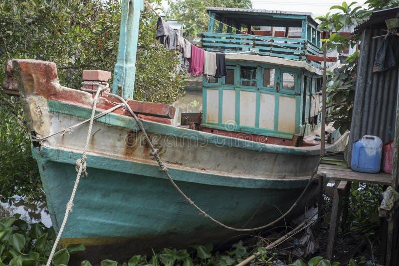 Barco de pesca de madera parqueado por una casa en un canal vietnamita fotos de archivo