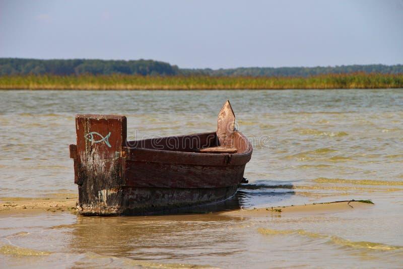 Barco de pesca marrón de madera del viejo vintage en el agua clara con horizonte fotos de archivo